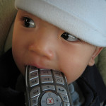 Baby chewing on a television remote control.