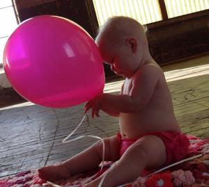 A baby holding a balloon.